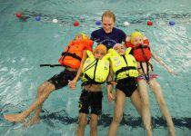 4 barn med svømmeinstruktør i flytevest