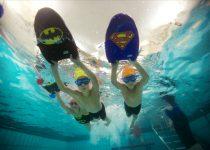 Barn som svømmer med plate tatt under vann